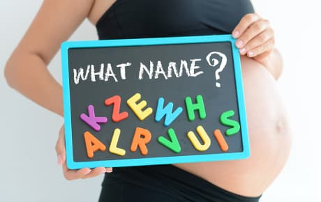 Young expectant mother with letter blocks spelling name on her p