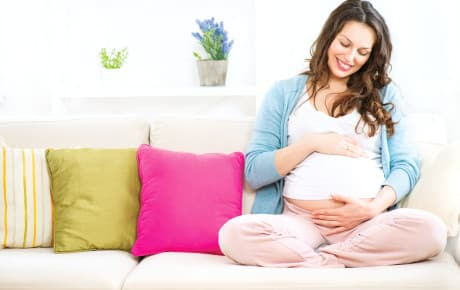 Pregnant woman sitting on a sofa and caressing her belly